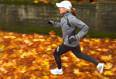 getty_rm_photo_of_woman_jogging_across_wet_leaves1